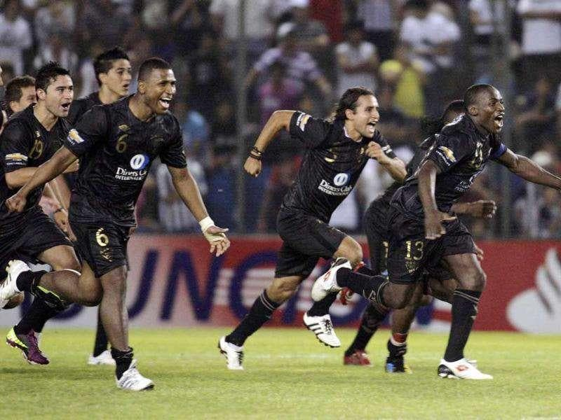 Players of Ecuador's LDU run towards their goalkeeper Alexander Dominguez (not pictured) to celebrate after he saved a penalty during their shootout against Paraguay's Libertad in a Copa Sudamericana soccer match in Asuncion.