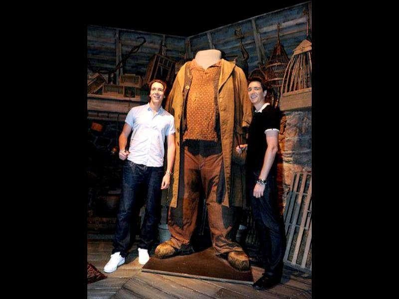 British twins James Phelps (L) and Oliver Phelps, who play Fred and George Weasley from the Harry Potter film series, stand beside Hagrid's costume during the opening of the Harry Potter exhibition at the Powerhouse Museum in Sydney. The show features hundreds of props, costumes and sets from the world's most successful film franchise.
