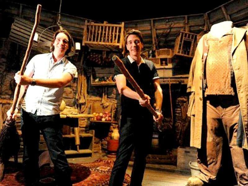 Twins James Phelps (L) and Oliver Phelps, who play Fred and George Weasley from the Harry Potter film series, play with broomsticks in Hagrid's hut during the opening of the Harry Potter exhibition at the Powerhouse Museum in Sydney.