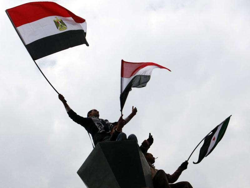 Demonstrators wave Egyptian flags and a Syrian 1946 independence flag (R) as they stand on an electricity pole during a protest at Tahrir Square in Cairo.