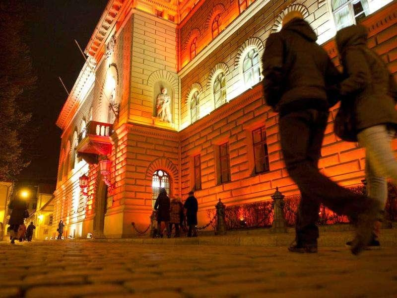 People walk by the light facility 'Parliament of Latvia' during the Staro Riga? light festival in Riga on November 17, 2011, to mark the Latvia's Independence Day. AFP Photo / Ilmars Znotins