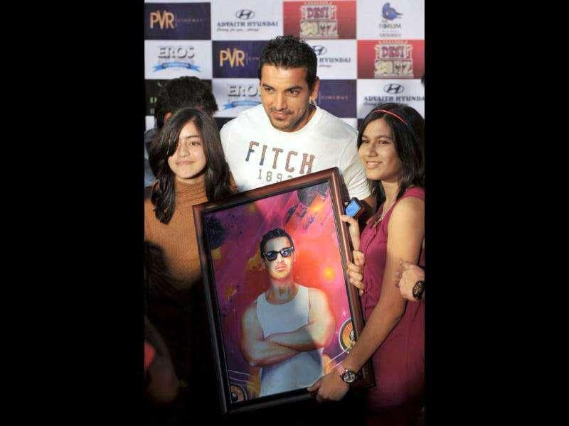 John Abraham poses for a photograph with fans after autographing his portrait during a promotional event held in Bangalore for Desi Boyz. (AFP)