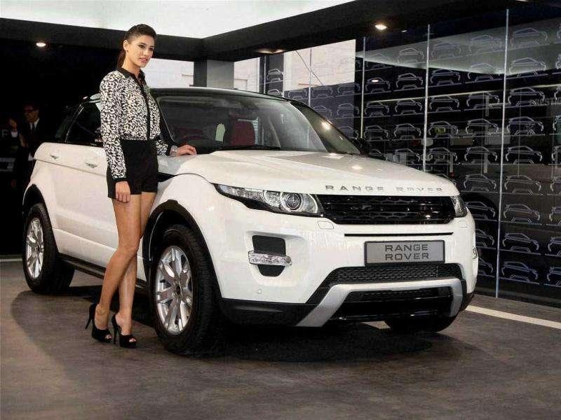 Nargis poses next to a white Range Rover Evoque.