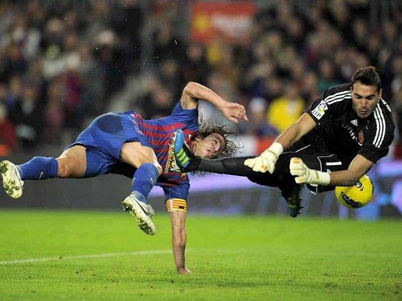 Barcelona's captain Carles Puyol (L) scores a goal to Zaragoza's goalkeeper Roberto (R) during their Spanish League football match at Camp Nou stadium in Barcelona. (AFP Photo/Lluis Gene)