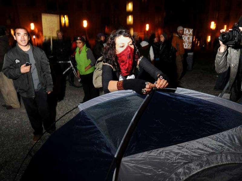 An Occupy Oakland protester, who declined to give her name, pitches a tent to establish a new encampment in Oakland, Calif. (AP Photo/Noah Berger)