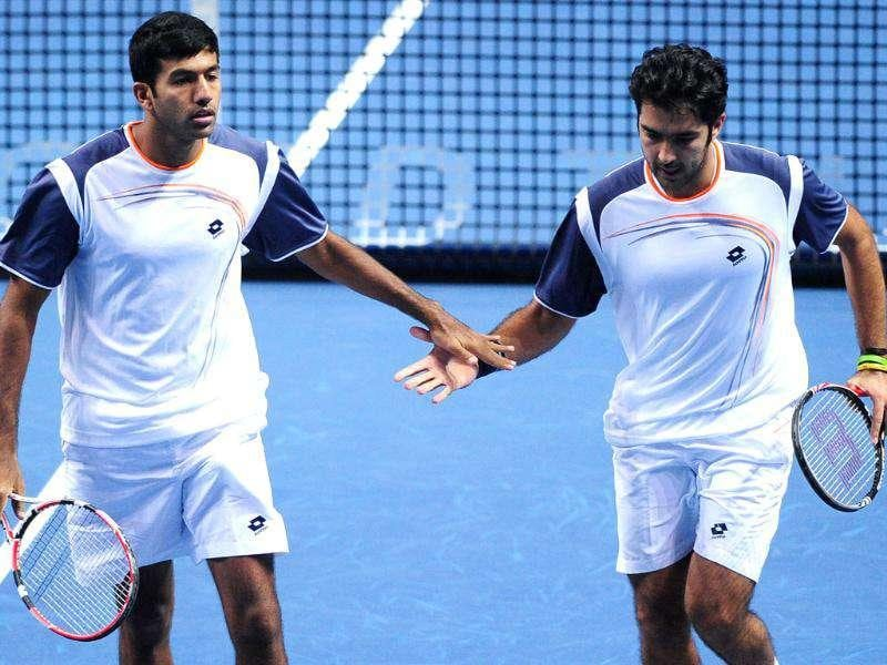 Aisam-ul-Haq Qureshi of Pakistan touches hands with Rohan Bopanna after a point against Max Mirnyi of Belarus and his partner Daniel Nestor of Canada during their group B doubles match at the ATP World Tour Finals tennis tournament in London.