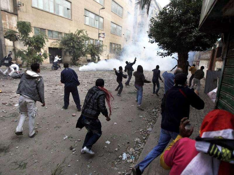 Protesters throw stones at Egyptian riot police during clashes near the interior ministry in downtown Cairo, Egypt.