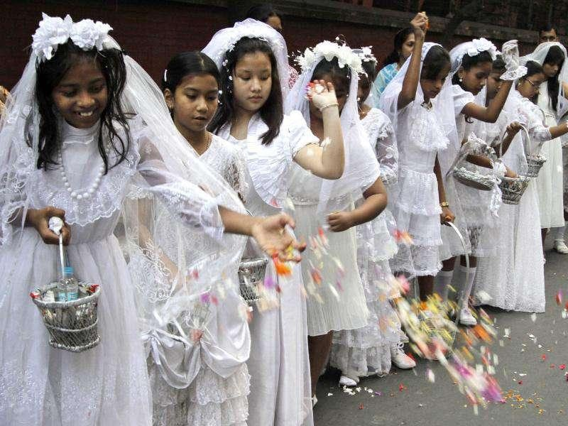 Catholic girls dressed as angels throw flower petals on road during a procession to mark the feast of Christ the King,a religious holiday celebrated on the last Sunday of the liturgical calendar in Kolkata.