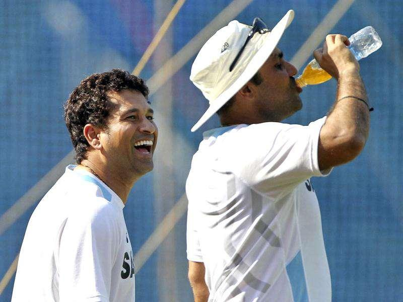 Sachin Tendulkar, left, looks at teammate Virender Sehwag who sips a drink during a training session ahead of their third Test cricket match against West Indies in Mumbai.