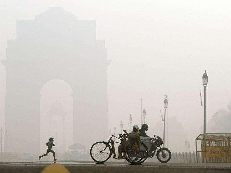 Commuters go past as a young child runs near India Gate, the war memorial in the morning fog, in New Delhi.