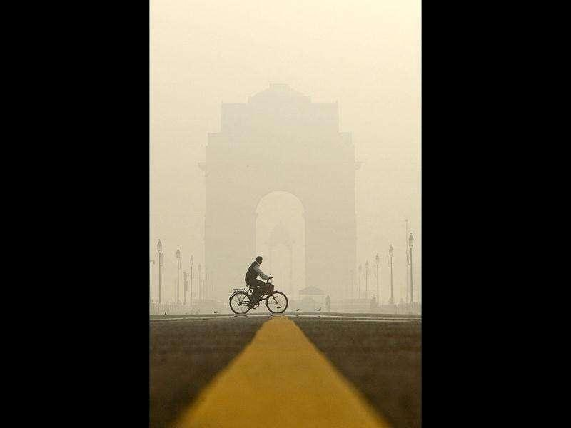 A man rides his bicycle through the morning fog near India Gate, the war memorial in New Delhi.