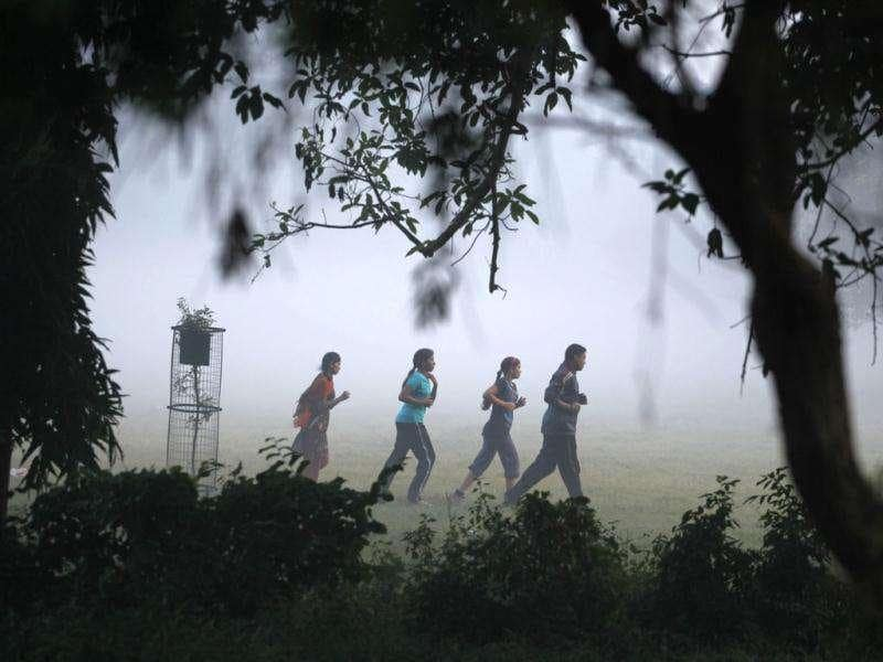 People jog through the early morning fog, in Allahabad. Dense fog over parts of north India caused disruption of rail services with scores of trains arriving several hours behind schedule.