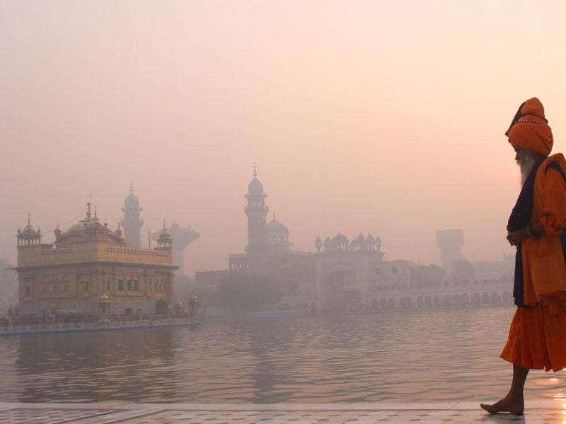 A devotee passing in front of Harmandar Sahib complex which was engulfed in season's first fog. HT Photo by Munish Byala