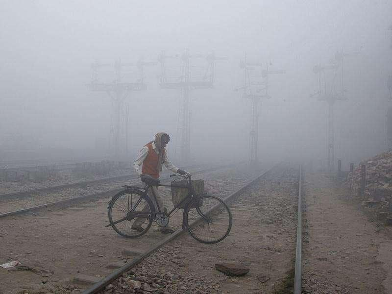 A man crosses a railway track with his bicycle amid dense fog on a cold morning in the northern Indian city of Allahabad. Reuters Photo