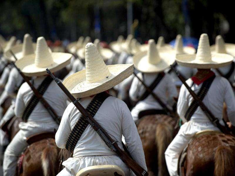 Men dressed as revolutionaries perform during a military parade commemorating the 101th anniversary of the Mexican Revolution along Reforma Avenue on November 20, 2011 in Mexico City. Mexico marks 101 years since the seven-year conflict began on Nov 20, 1910 that saw peasant armies led by heroes Emiliano Zapata and Pancho Villa topple the dictatorship of Porfirio Diaz. AFP Photo/Yuri Cortez