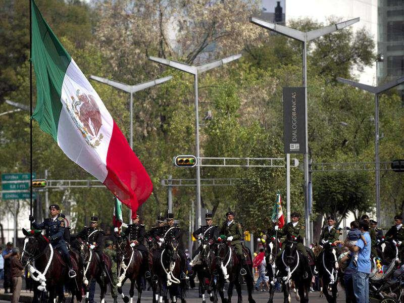 Soldiers ride horses during a military parade commemorating the 101th anniversary of the Mexican Revolution along Reforma Avenue in Mexico City. AFP Photo
