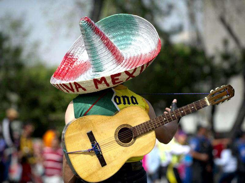 A man using a traditional Mexican hat, holds his guitar as he observes a military parade commemorating the 101th anniversary of the Mexican Revolution along Reforma Avenue in Mexico City. AFP Photo