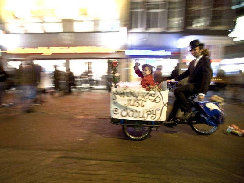 Newly-weds Eveline Constance Heijkamp (L) and Gijs Peskens, Occupy Amsterdam demonstrators, leave on a bicycle after getting married on the Beursplein in Amsterdam.