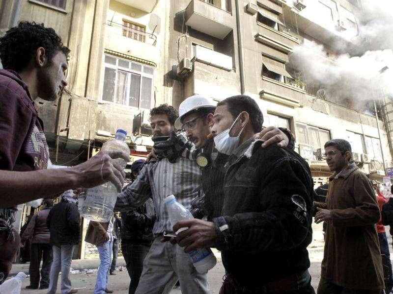 Egyptian protesters help an injured journalist, Maher Malak, from the scene of a building fire, seen in background, near Tahrir Square in Cairo. AP Photo/Amr Nabil