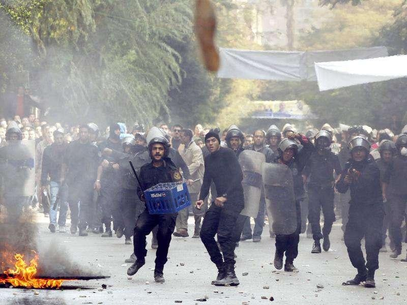 Protesters throw a shoe during clashes with riot police in a side street near Tahrir Square in Cairo. Photo: Reuters/Goran Tomasevic