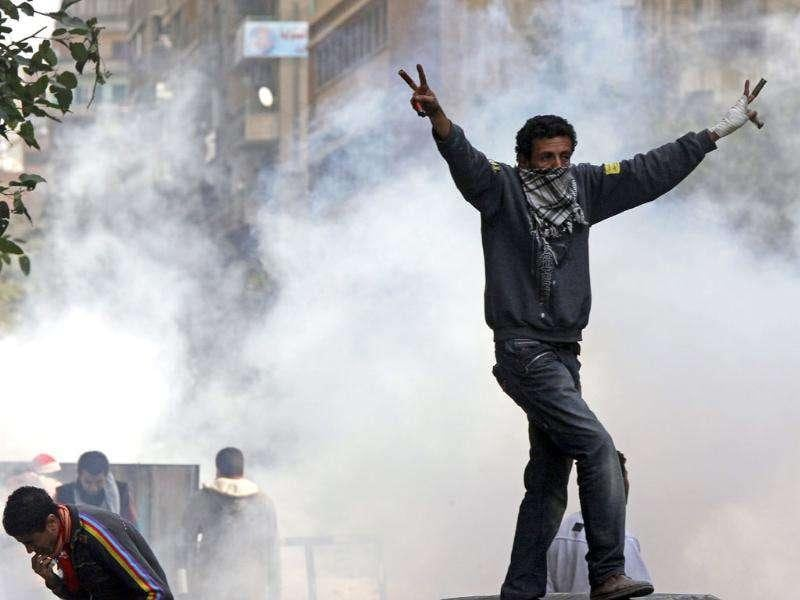 A protester makes a victory sign during clashes with riot police in a side street near Tahrir Square in Cairo. Photo: Reuters/Goran Tomasevic