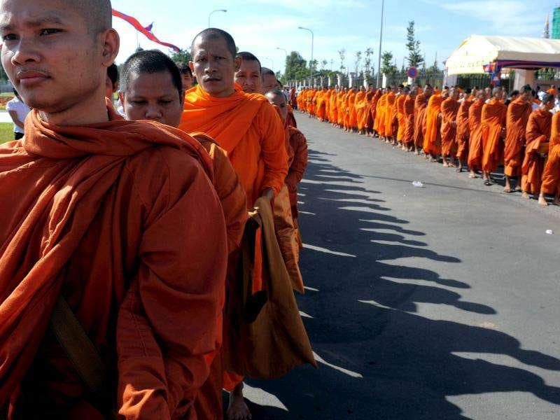 Cambodian Buddhist monks line up to get food during the inauguration ceremony of a memorial stupa for victims of a bridge stampede in Phnom Penh. More than 350 people died in a bridge stampede during the annual Water Festival in November 2010. AFP PHOTO / TANG CHHIN SOTHY