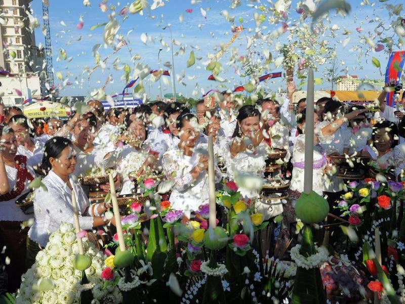 Cambodian government officials and people throw flowers during the inauguration ceremony of a memorial stupa for victims of a bridge stampede in Phnom Penh. More than 350 people died in a bridge stampede during the annual Water Festival in November 2010. AFP PHOTO / TANG CHHIN SOTHY