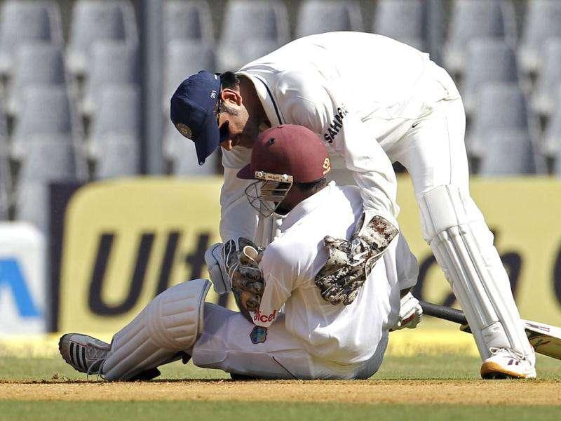 Mahendra Singh Dhoni (top) speaks to West Indies' Adrian Barath after they collided during their third Test cricket match in Mumbai.