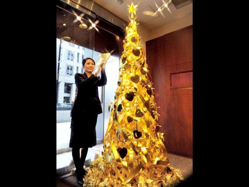 An employee of Japanese jeweller Tanaka Kikinzoku Jewelry unveils a 150 million yen ($1.95 million) Christmas tree which will be on display till Christmas Day at the company's main shop in Tokyo. The 2.4 meter tall Christmas tree is decorated with heart and orchid shaped ornaments, ribbons and a star made of gold. AFP PHOTO/Yoshikazu TSUNO