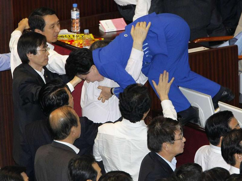 Lawmakers of opposition parties help their fellow lawmaker (top) who tries to escape as they scuffle with lawmakers of the ruling Grand National Party (GNP) at the National Assembly plenary session hall in Seoul on December 8, 2010. The opposition lawmakers were trying to prevent GNP lawmakers from passing new bills, including the new year's budget bill.