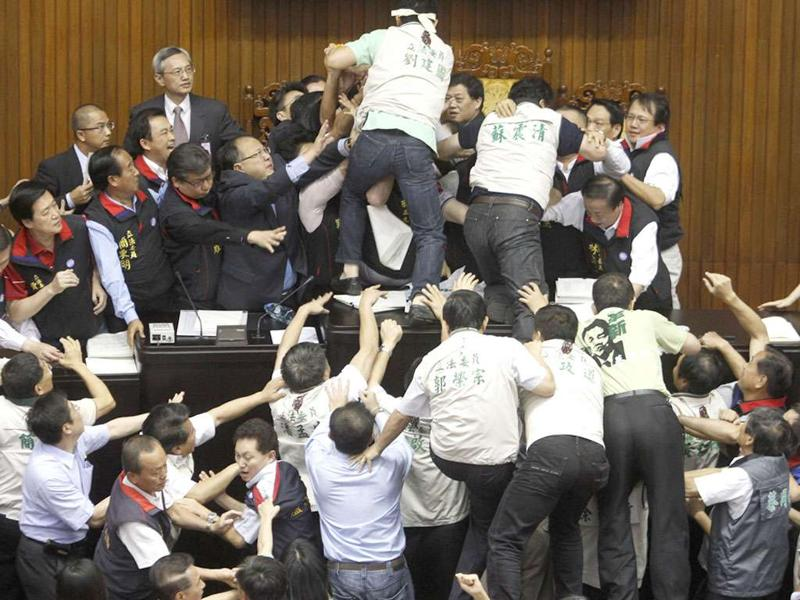 Opposition Democratic Progressive Party (DPP) legislators scuffle with ruling Nationalist Party (KMT) legislators (top) at the Legislative Yuan in Taipei on July 8, 2010. Taiwan legislators threw objects, splashed water and kicked one another on Thursday, sending the two to the hospital in a brawl over how fast to ratify a trade pact with China that is shaping up as a pivotal election issue.