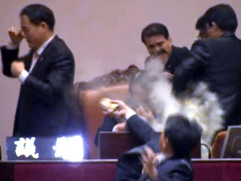 Rep. Kim Seon-dong, bottom, of the opposition Democratic Labor Party, explodes tear gas in front of the speaker's chair to block National Assembly Vice Speaker Chung Eui-hwa, center, from pushing for the procedure to handle a pending bill on ratification of a South Korea-US free trade agreement at the National Assembly in Seoul, South Korea, on Nov 22, 2011.
