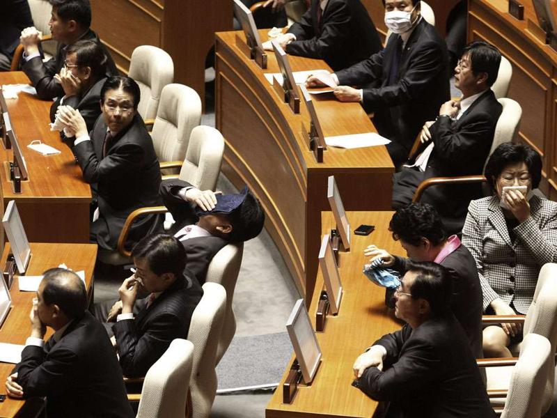 South Korean lawmakers cover their mouths after an opposition lawmaker exploded tear gas to block the passing a bill on ratification of a Korea-US free trade agreement at the National Assembly in Seoul, South Korea on Nov 22, 2011.