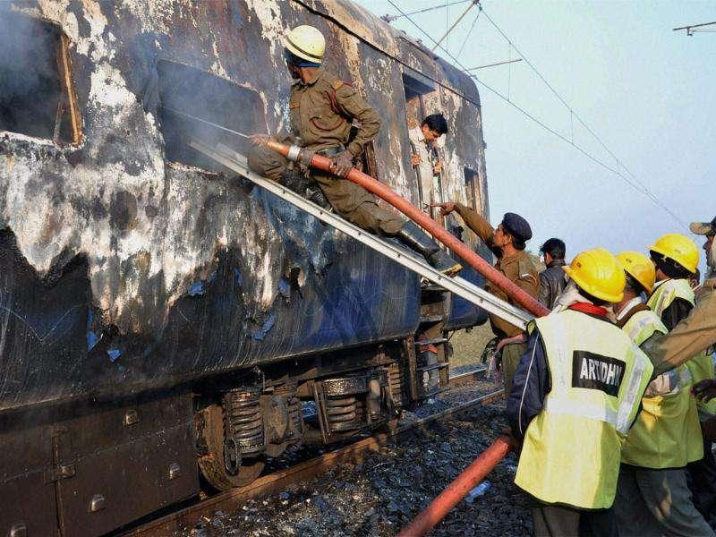 Firemen extinguishing the fire in one of the two AC coaches of the Howrah-Dehradun Express train in Giridih district of Jharkhand. PTI Photo