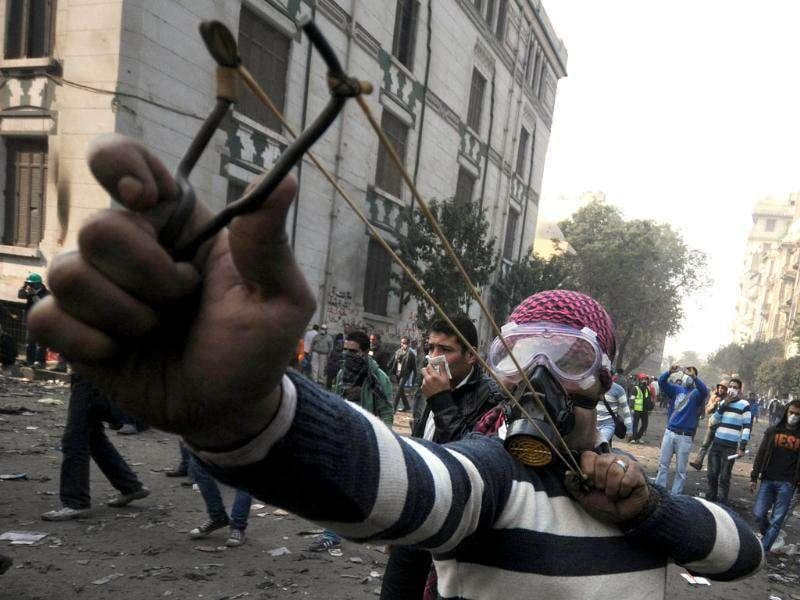An Egyptian youth wearing a gas mask aims a sling shot during clashes in Cairo. AFP Photo/Mohammed Hossam