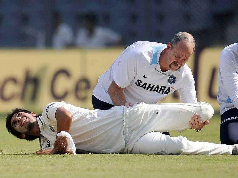 A physiotherapist helps Ishant Sharma (on ground) to stretch during the second day of the third test cricket match between India and West Indies at the Wankhede stadium in Mumbai.