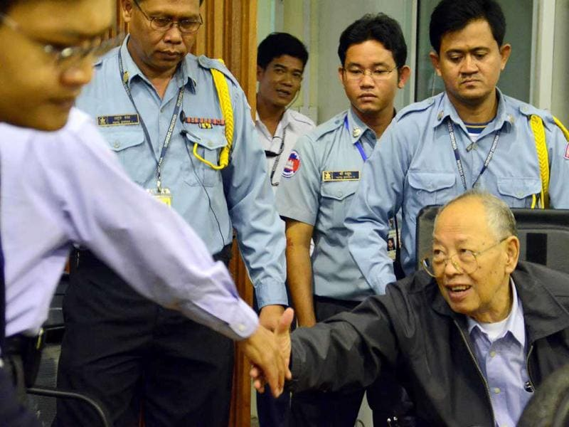 This handout photo taken and released by the Extraordinary Chamber in the Courts of Cambodia (ECCC) shows former Khmer Rouge deputy prime minister and minister of foreign affairs Ieng Sary (R) shaking hands with an official in the courtroom at the ECCC in Phnom Penh. Two top Khmer Rouge leaders accused of genocide and other atrocities were expected to address Cambodia's war crimes court, a day after the third co-defendant in their trial said the allegations against him are 'not true'.