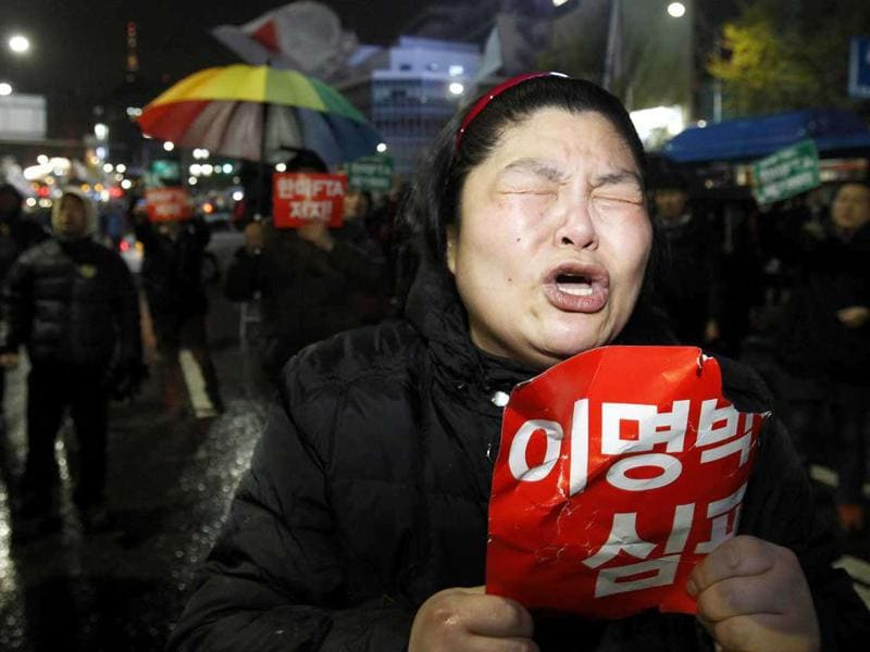 A protester cries as she denounces the passing of the bill on ratification of the Korea-US free trade agreement in Seoul, South Korea, Tuesday. South Korea's parliament ratified a long-stalled free trade deal with the United States on Tuesday after ruling party lawmakers forced a vote amid shouts and shoves from opposition rivals.