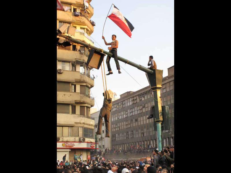 An Egyptian protester hangs an effigy representing Egypt's military ruler, Field Marshal Mohamed Hussein Tantawi, the head of SCAF, The Supreme Council of the Armed Forces, at Tahrir Square in Cairo.