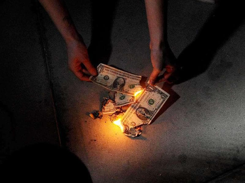 Protesters burn US one dollar bills during an Occupy Los Angeles demonstration and march at the Federal Reserve Bank of Los Angeles. The march and rally were part of a nationwide protest against the twelve Federal Reserve Banks.