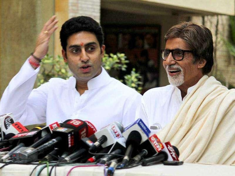Amitabh Bachchan, right, laughs as his son Abhishek Bachchan speaks during a press conference in Mumbai. (AP Photo)