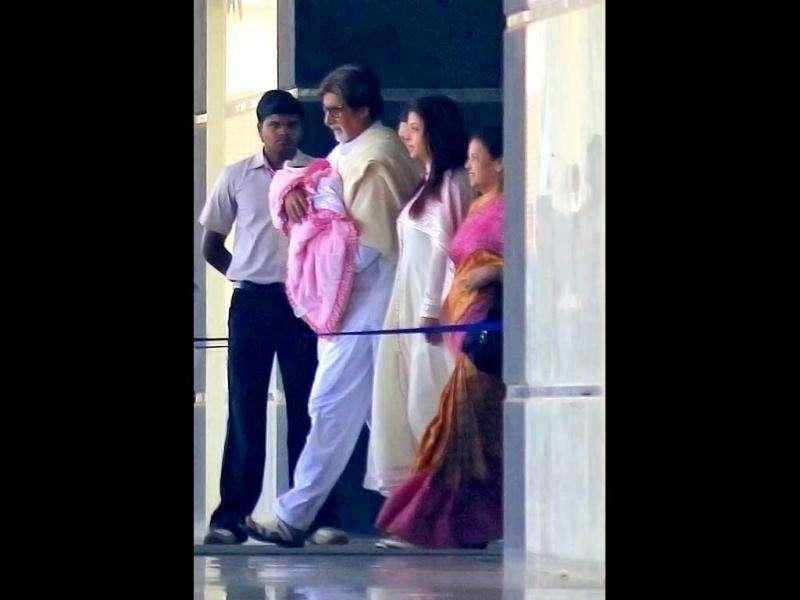 Amitabh Bachchan walks out of a hospital holding his grand-daughter. (AP Photo)