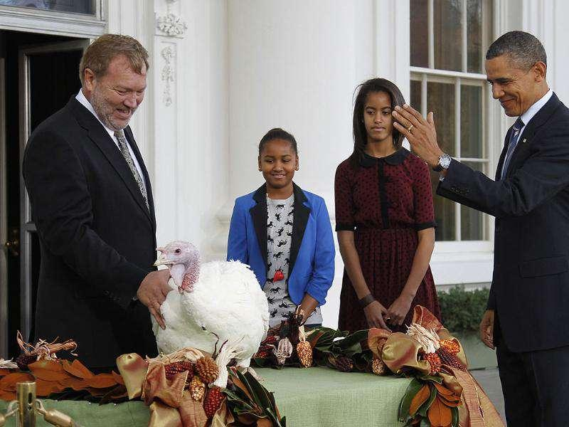 US President Barack Obama (R) pardons the 2011 Thanksgiving Turkey, Liberty, alongside his daughters Sasha (2nd L) and Malia on the North Portico of the White House in Washington.