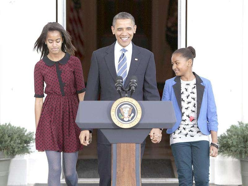 US President Barack Obama walks with daughters Sasha and Malia before he pardoned Liberty, a 19-week old, 45-pound turkey, on the occasion of Thanksgiving in Washington.