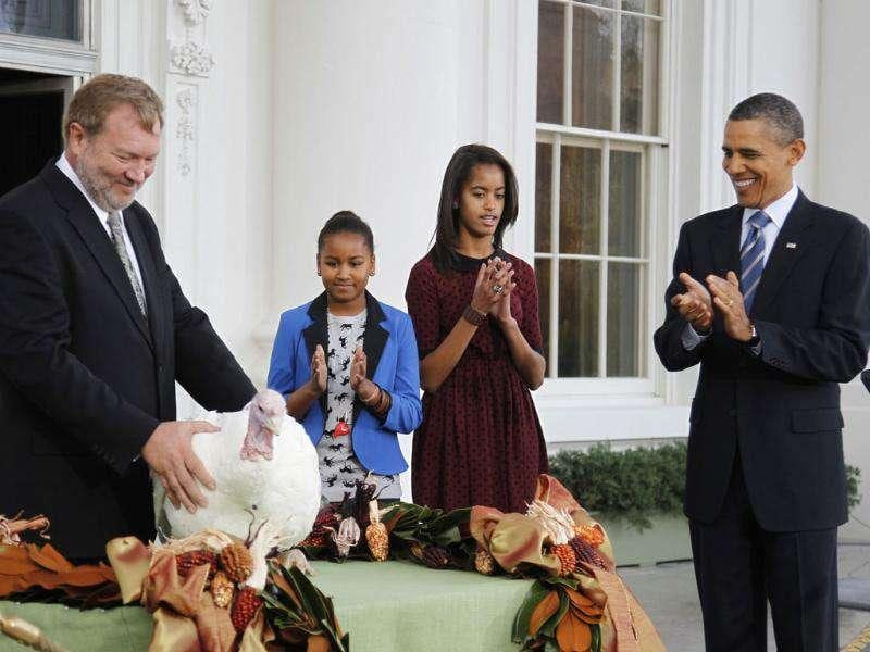 US President Barack Obama (R) pardons the 2011 Thanksgiving Turkey, Liberty, alongside his daughters Sasha (2nd L) and Malia on the North Portico of the White House.