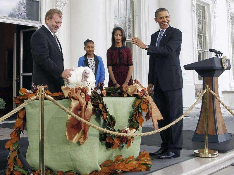 US President Barack Obama, with daughters Sasha and Malia, pardons Liberty, a 19-week old, 45-pound turkey, on the occasion of Thanksgiving in White House.