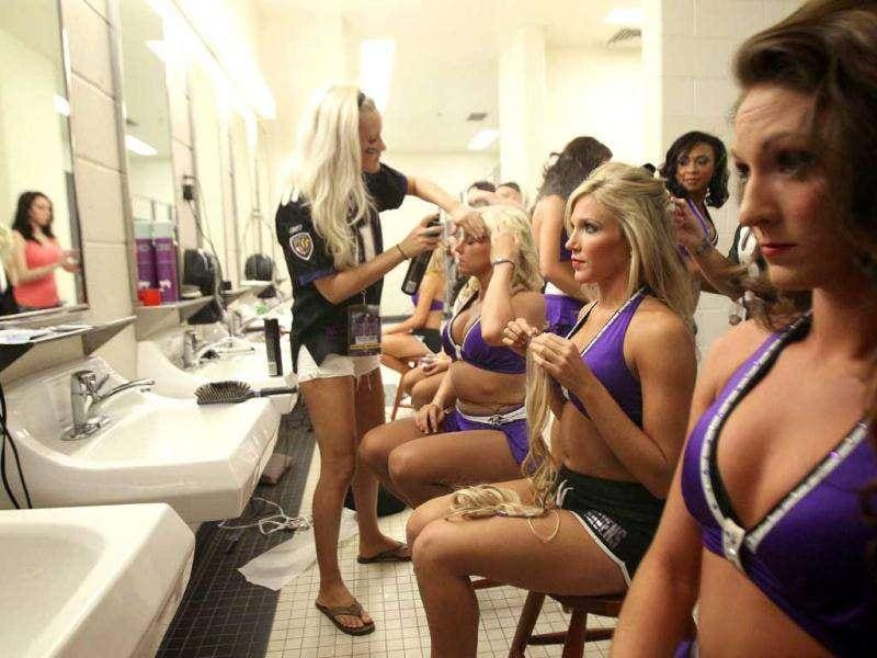 Baltimore Ravens cheerleaders have their hair done during prep in the locker room prior to a Ravens NFL football game.