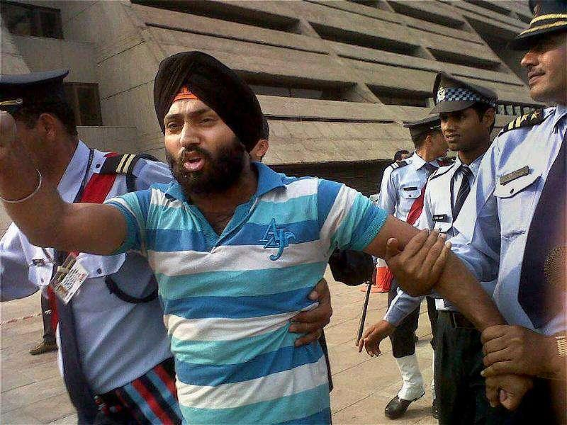 Security take away a youth, identified as Harvinder Singh after he slapped union agriculture minister Sharad Pawar at NDMC in New Delhi on Thursday. (PTI)