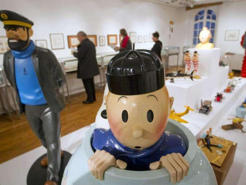 A statue of the comic character Tintin (C) signed by sculptor Jean-Marie Pigeon at the Artcurial auction house in Paris. Sculptures, drawing, comics and objects from the Tintin world are presented two days before the Hergé auction, creator of the Franco Belgian comic.