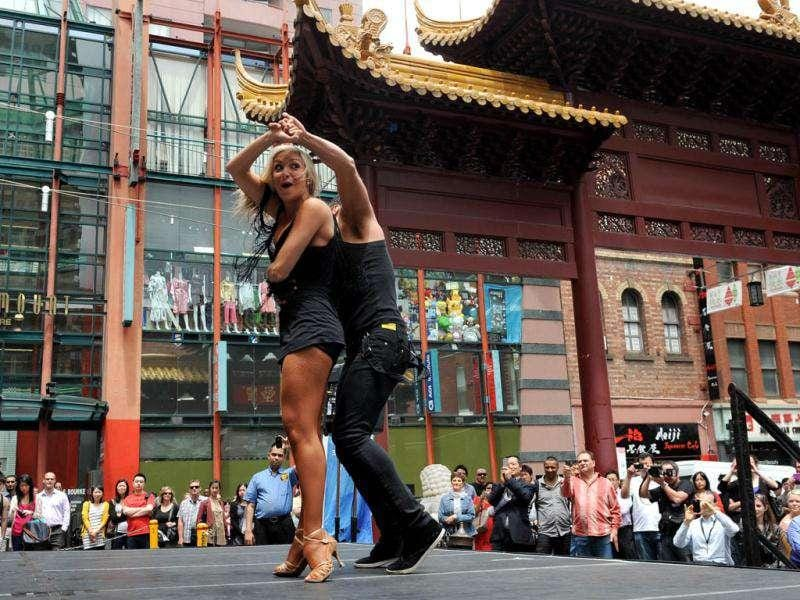 Jessica Raffa (L) and Carmelo Pizzano (R) dance in Melbourne's Chinatown in front of the lunchtime crowds, to promote the upcoming WDSF Asian Pacific DanceSport Championships.